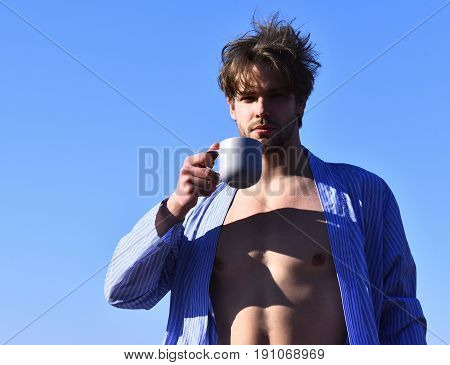 Bearded man short beard. Caucasian macho with moustache and ruffled hair in blue striped pajamas showing strong torso with six packs and holding cup on blue sunny sky background morning concept