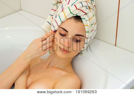 beautiful girl with a towel on your head relaxes in bath with foam at home