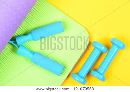 Concept of sports as lifestyle with lightweight dumbbells and blue skipping rope on green and violet yoga mat isolated on yellow background top view. Sport in trend