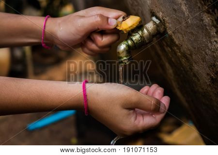 Close up Asian boy open metal water faucet empty land. Water is life concept.