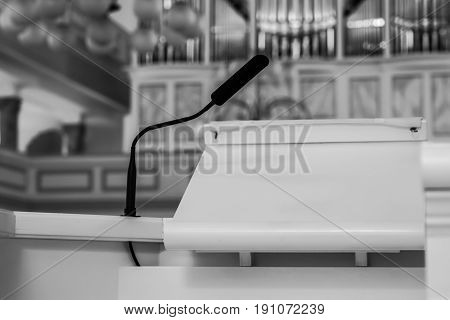 Empty pulpit in the church with an organ at the background, black and white