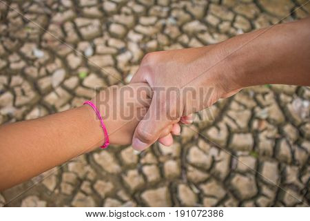 Father and children hold hands to help each other across the drought Drought concept.