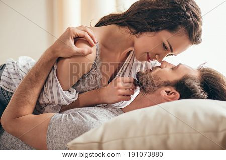 Close-up Portrait Of Beautiful Sensual Young Couple Hugging While Lying On Bed And Looking At Each O