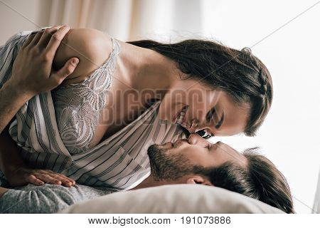 Close-up View Of Passionate Young Couple In Love Lying On Bed And Hugging