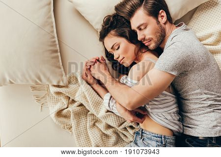 Top view of beautiful happy young couple hugging while sleeping on bed