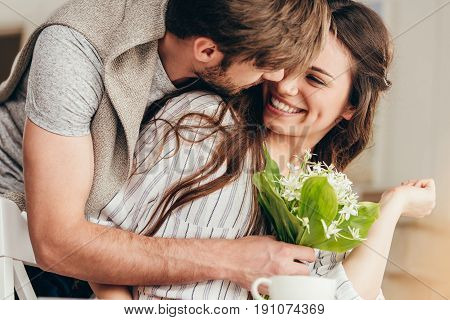 young casual couple embracing with bouquet of flowers at home