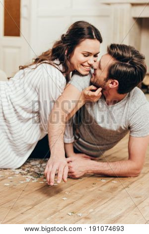 Young Smiling Couple Able To Kiss While Lying On The Floor At Home