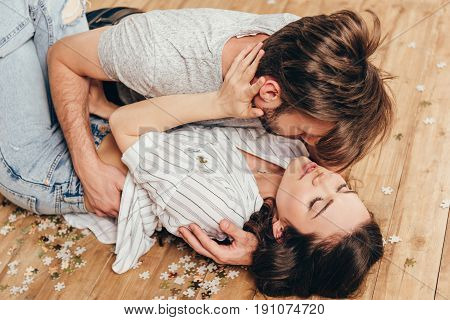 Young Sensual Couple Hugging And Able To Kiss While Lying On The Floor At Home