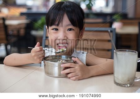 Asian Chinese little girl eating steamed minced pork and rice at outdoor restaurant