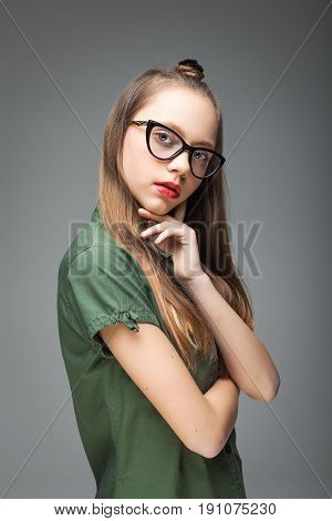 young pretty brunette spectacled girl over gray background. woman dressed in green T-shirt and black jeans. red lips.