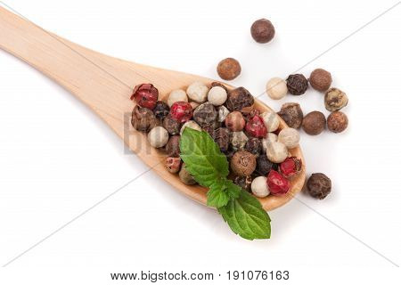 Mixture of peppers hot, red, black, white and green pepper in a wooden spoon isolated on white background. Top view.