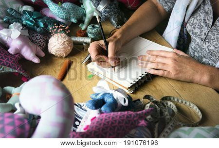 Closeup of hands drawing doll pattern handicraft