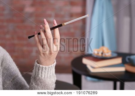 Female hand with cigarette holder on blurred background