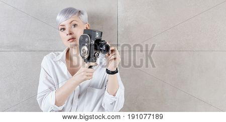 Attractive young woman filming with retro movie camera,