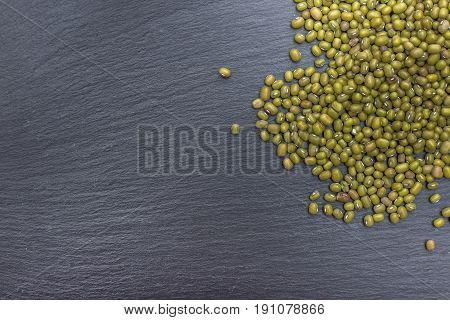 Green mung bean on black background of slate or stone. Top view