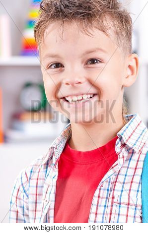 close up portrait of happy smiling young boy looking at camera. Child in the classroom or home.