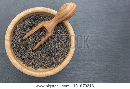 Black wild rice and olive wood scoop in a wooden bowl on black background of slate or stone
