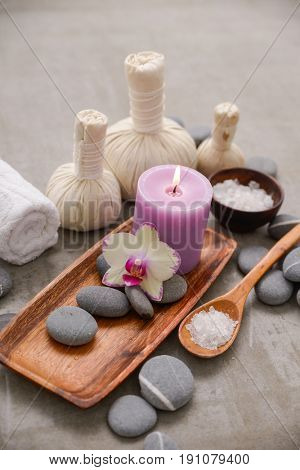 pink orchid with candle, herbal ball in basket with towel,stones on gray background