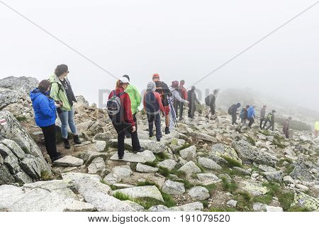 HIGH TATRAS, SLOVAKIA - JUNE 11: Tourists in the mountains go and look at the beautiful nature. Filmed on a foggy day, on June 11, 2017 in High Tatras, Slovakia.