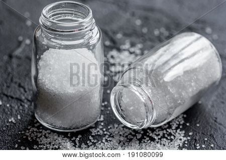 salt in glass saltcellar on black stone kitchen table background