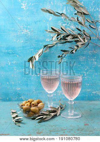 Glasses of wine on the aquamarine background and olives.