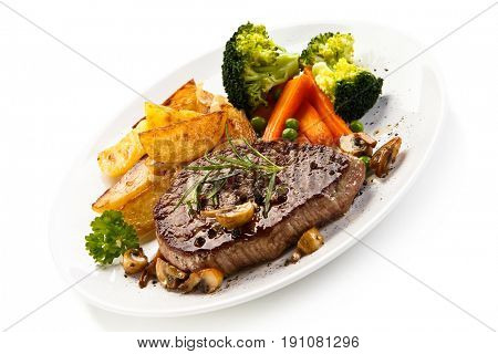 Grilled beefsteak with broccoli and carrot on white background