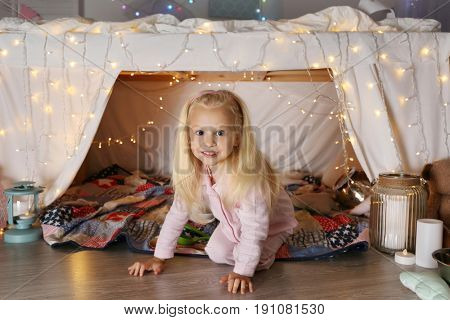 Cute funny girl getting out of hovel at home