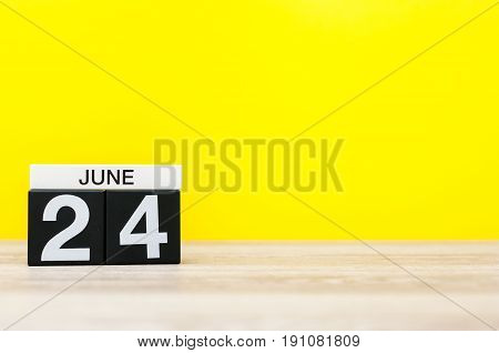 June 24th. Day 24 of month, calendar on yellow background. Summer day. Empty space for text.