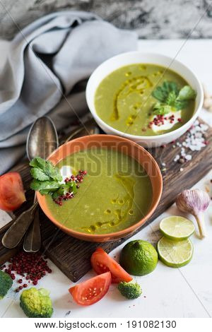 Bowl of green broccoli soup with sour cream and pepper