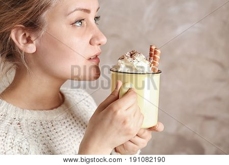 Woman holding metal mug and tasting delicious cocoa drink with whipped cream, close up
