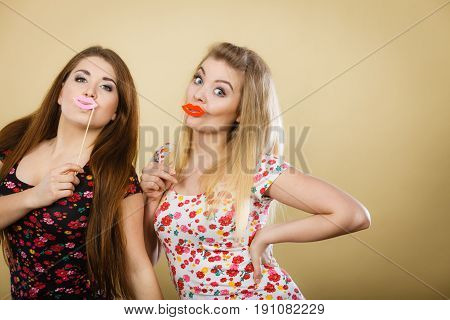 Two Happy Women Holding Fake Lips On Stick