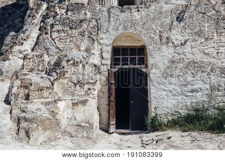 Ancient wooden door in the white chalky mountain, the entrance to the hollowed temple inside, Divnogorie, Voronezh region, Russia