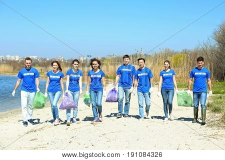 Young volunteers with garbage bags near river
