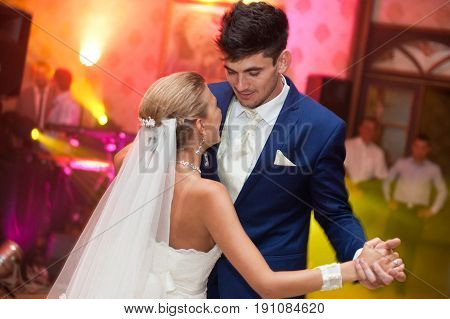 Tall Groom Admires A Tiny Blonde Bride During The Dance