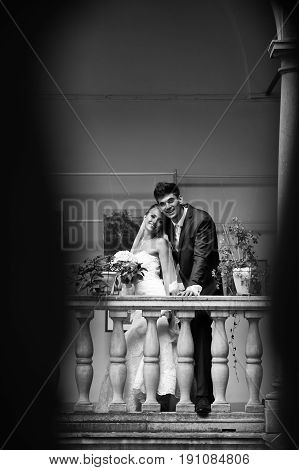 A Look From Afar On A Happy Wedding Couple Holding Their Hands Together While Posing On The Balcony