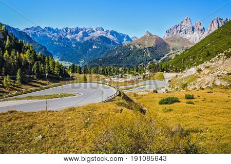Autumn in the Tirol. Sharp turn of the road on the Sella Pass, Dolomites. The concept of ecological and extreme tourism. Impressive ridge of dolomite rocks