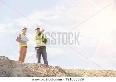 Low angle view of supervisors discussing at construction site against sky