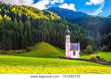 The famous church of St. Mary Magdalene and bell tower in a mountain valley. Dolomites, Tyrol, summer sunset. The concept of eco-tourism