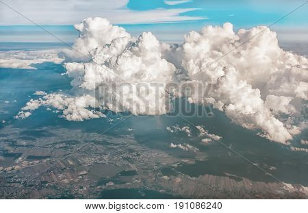 Views of clouds and land from airplane window from a height. The horizontal frame. Tone.
