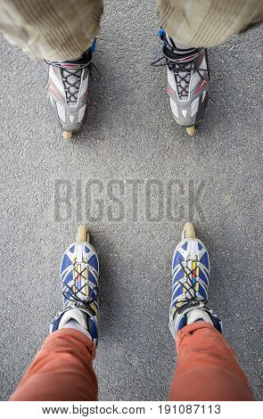Man and a woman on roller skates standing opposite each other. Top view.