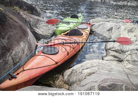Two kayaks are moored on the rocky shore of the sea.