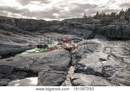 Two kayaks are moored on the rocky shore in the background you can see the old wooden bridge cloudy sky and forest.