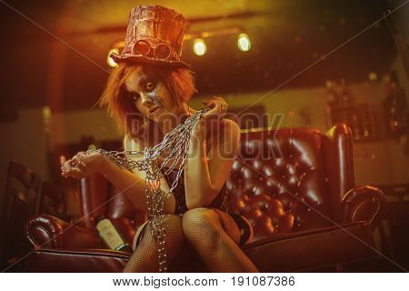 Redhaired girl sitting on sofa with chains in her hands and hat and glasses.  Studio photo