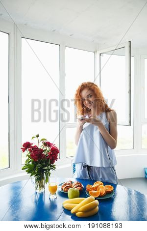 Image of young happy redhead lady standing near table indoors take a photo with phone of fruits and croissant. Looking at camera.
