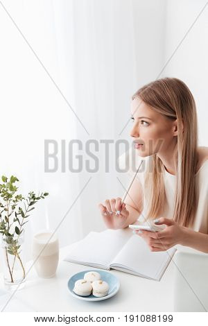 Image of young woman sitting indoors near sweeties holding mobile phone. Looking aside.