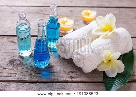 Spa wellness setting in blue yellow and white colors. Bottles wih essential aroma oil candles and towels on wooden background. Selective focus.