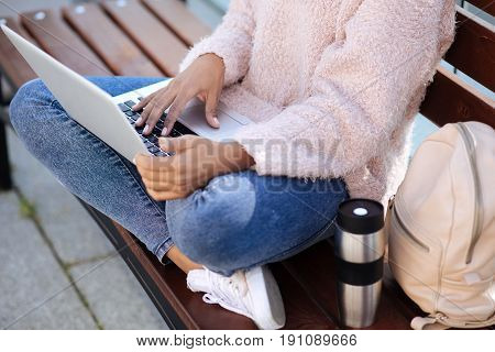 Pros of mobility. Attentive intelligent productive girl catching the moment of nice weather and sitting in park while working on her uni assignment on her laptop