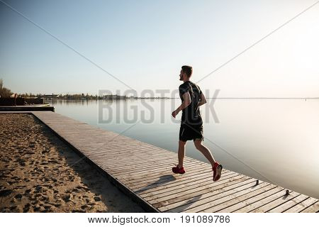 Back view full length portrait of a young sportsman running on the beach in the morning