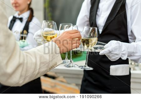 Midsection of professional waiter in uniform serving wine during buffet catering party, festive event or wedding. Full glasses of champagne on tray. Outdoor party catering service, waiter on duty