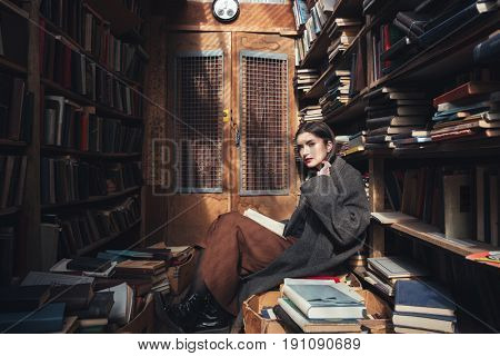 Full length portrait of a young woman in coat holding book while sitting on the floor in an old library